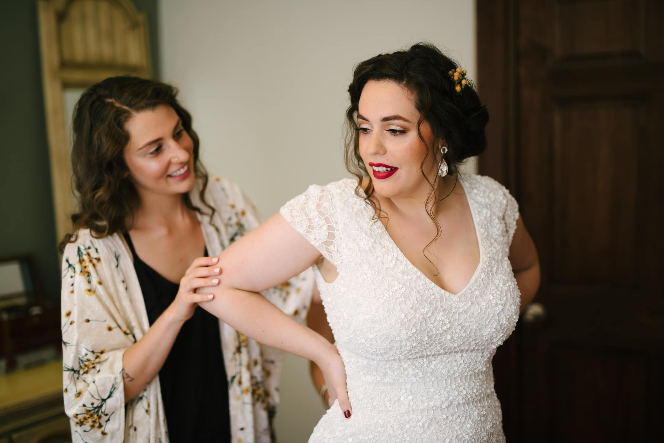 Jessica with her sister getting into wedding dress in Oakland apartment
