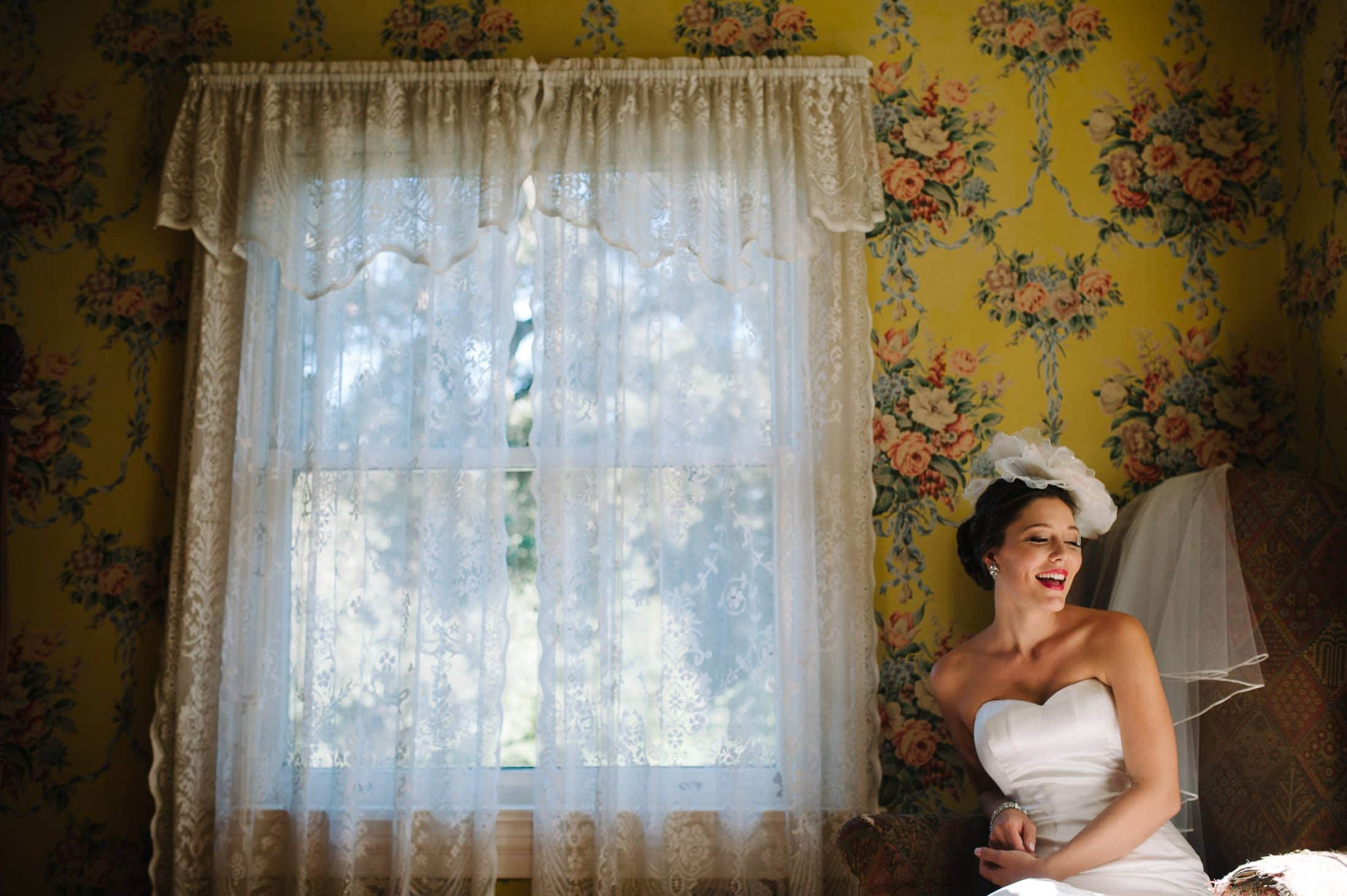 fun shot of bride against floral wall paper at Atherton Wedding