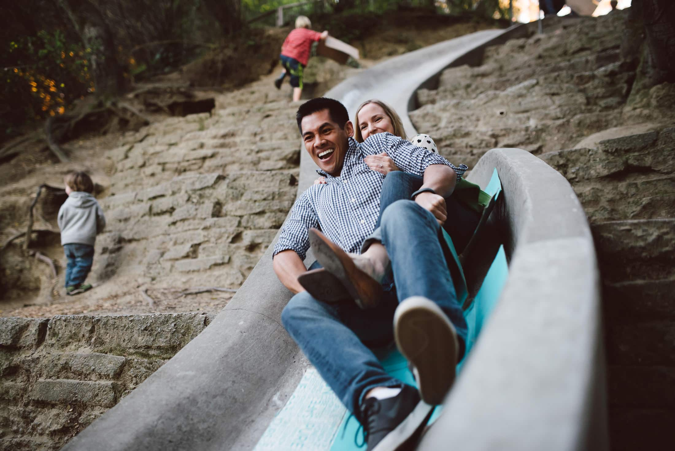 Engagement couple on slide in codornices park in berkeley