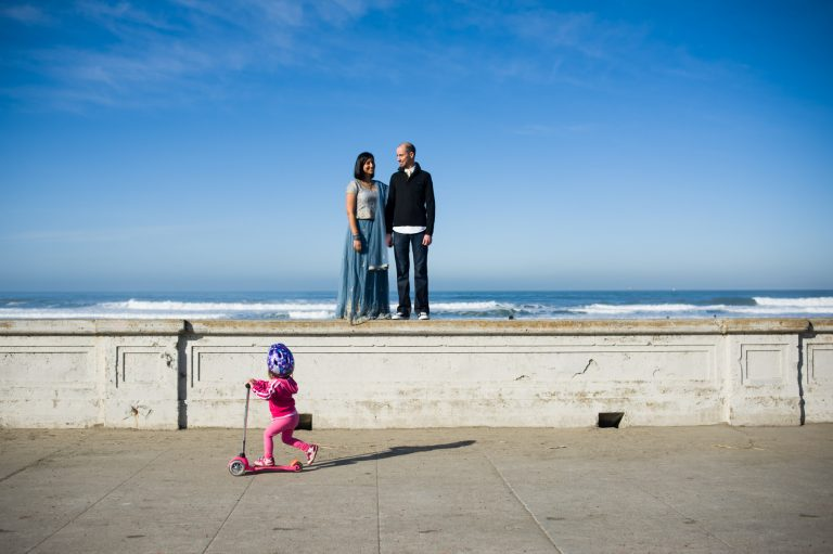 Kids ridding in front of couple at san francisco engagement