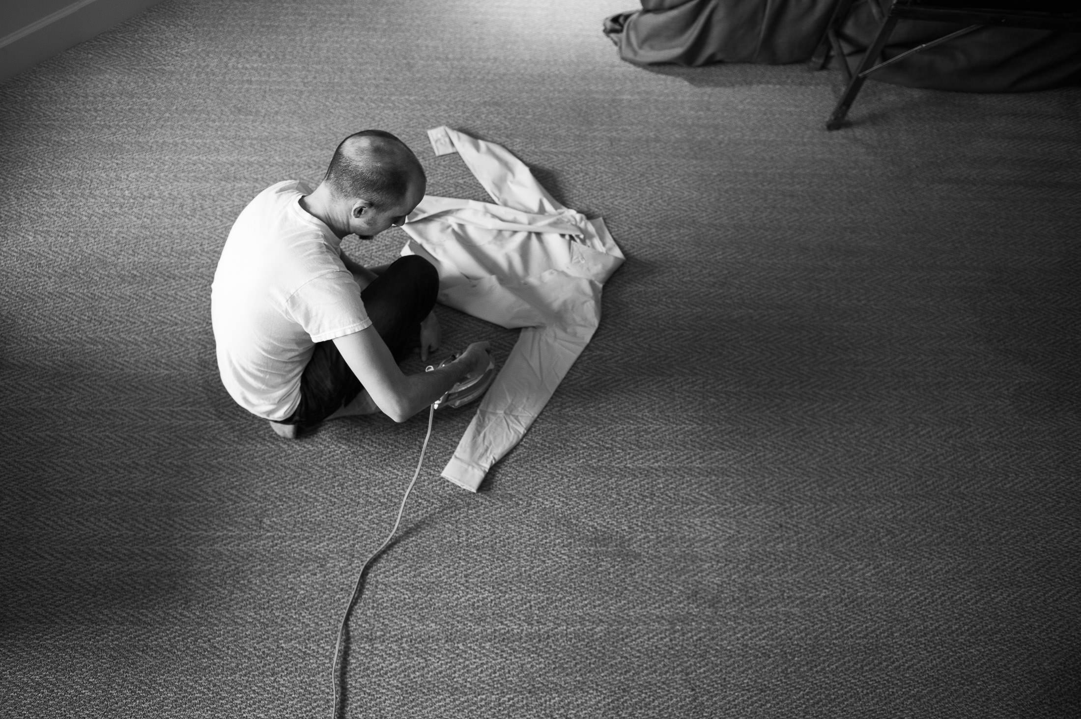 groom ironing shirt before wedding at Ramekins Culinary School