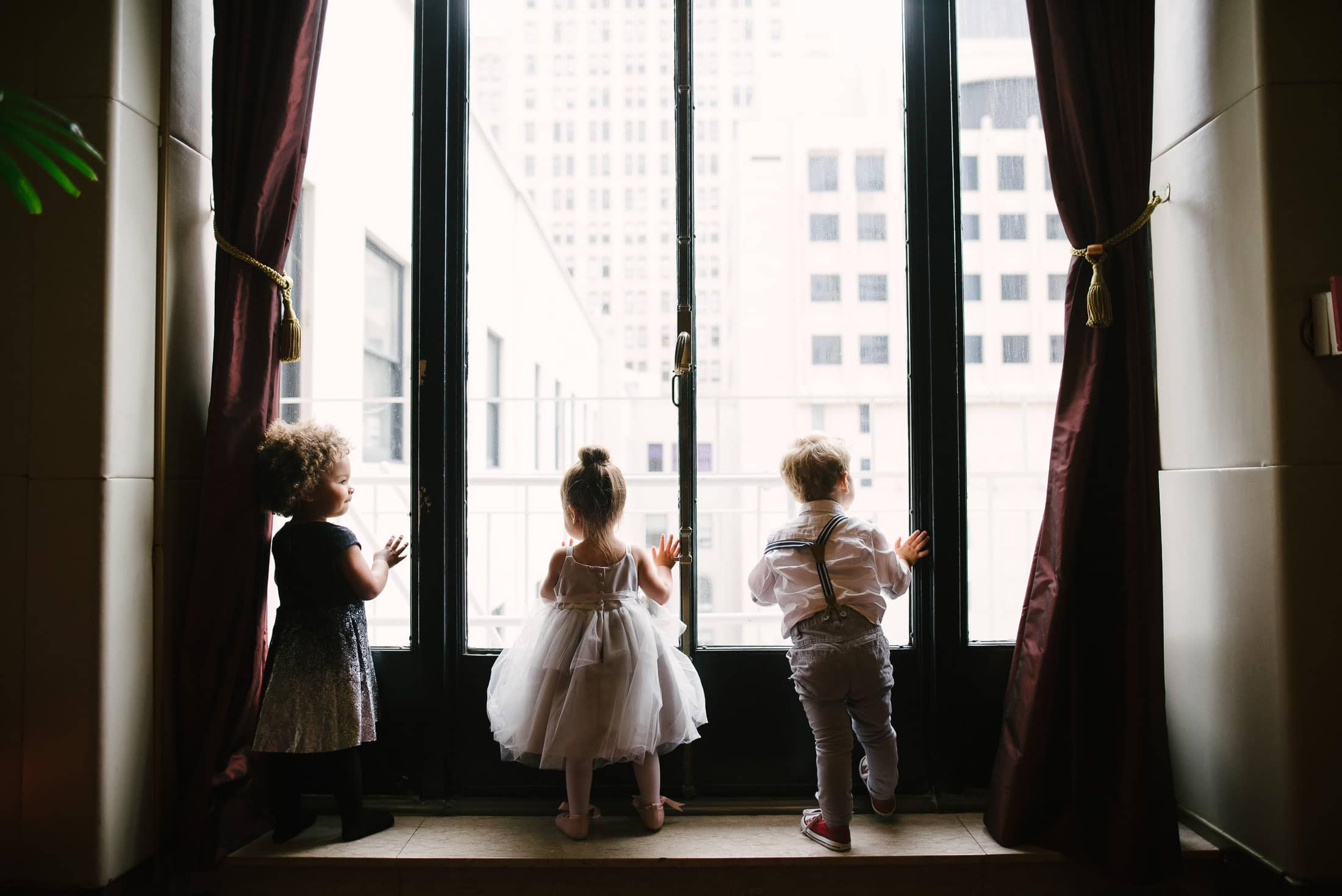 Kids looking out window at wedding at SF City Club