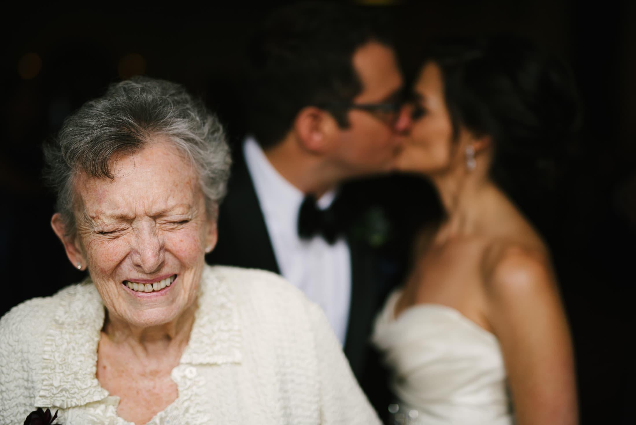 Grandma laughing while couple kiss at SF City Club