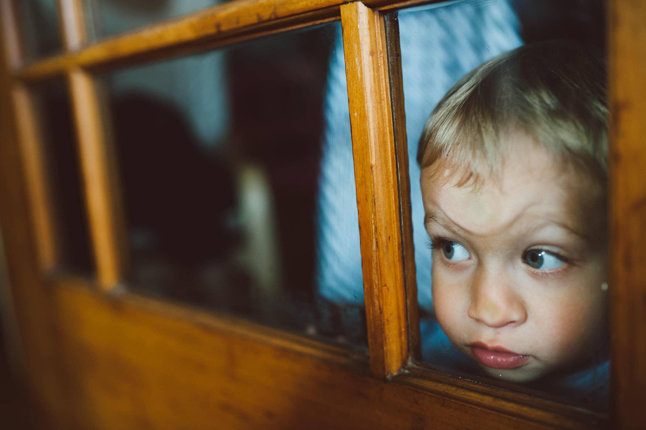 kid pressing head against glass at san francisco family shoot
