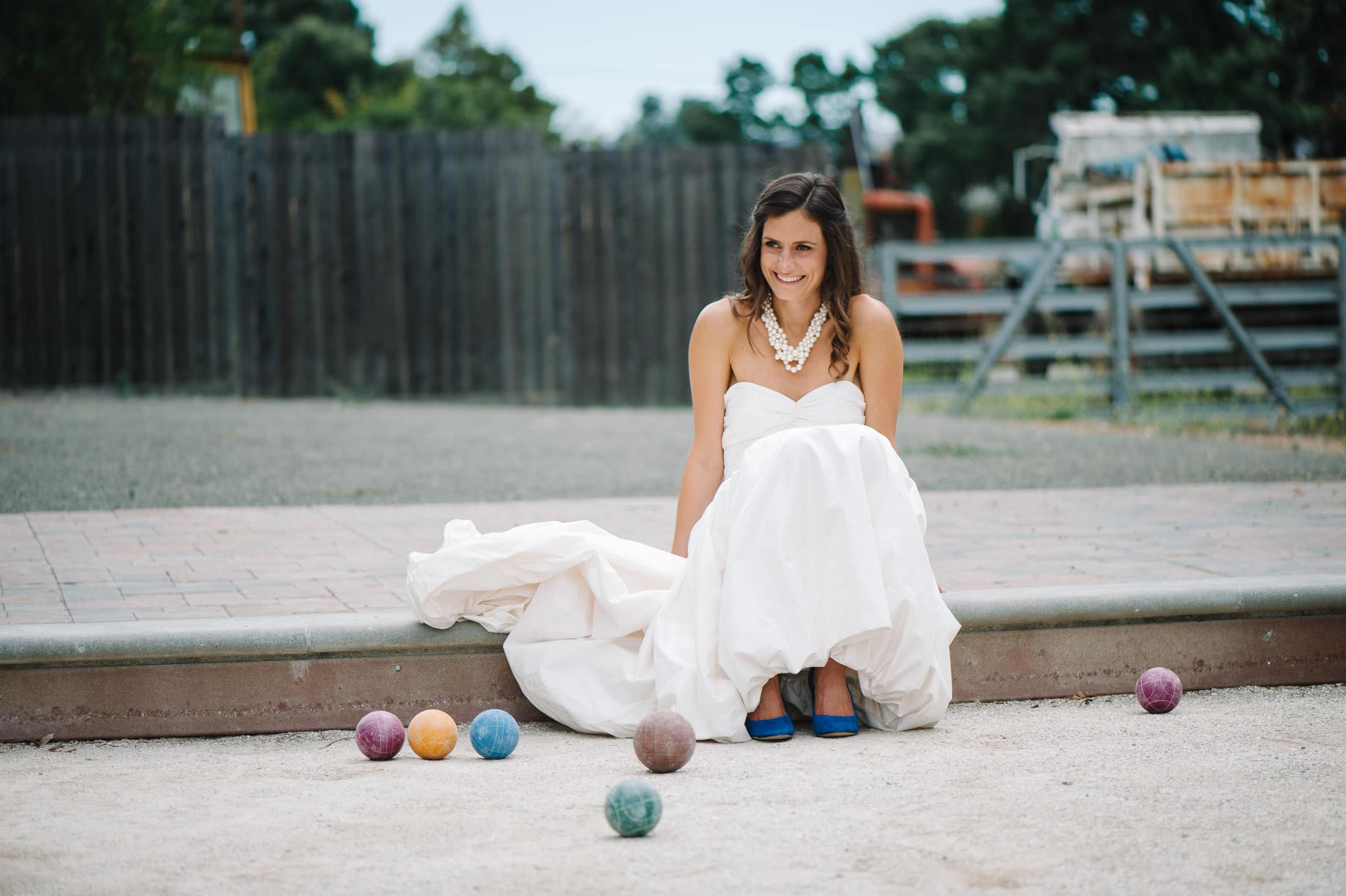 Fun portrait of bride in bocci ball court at sonoma garden pavilion wedding