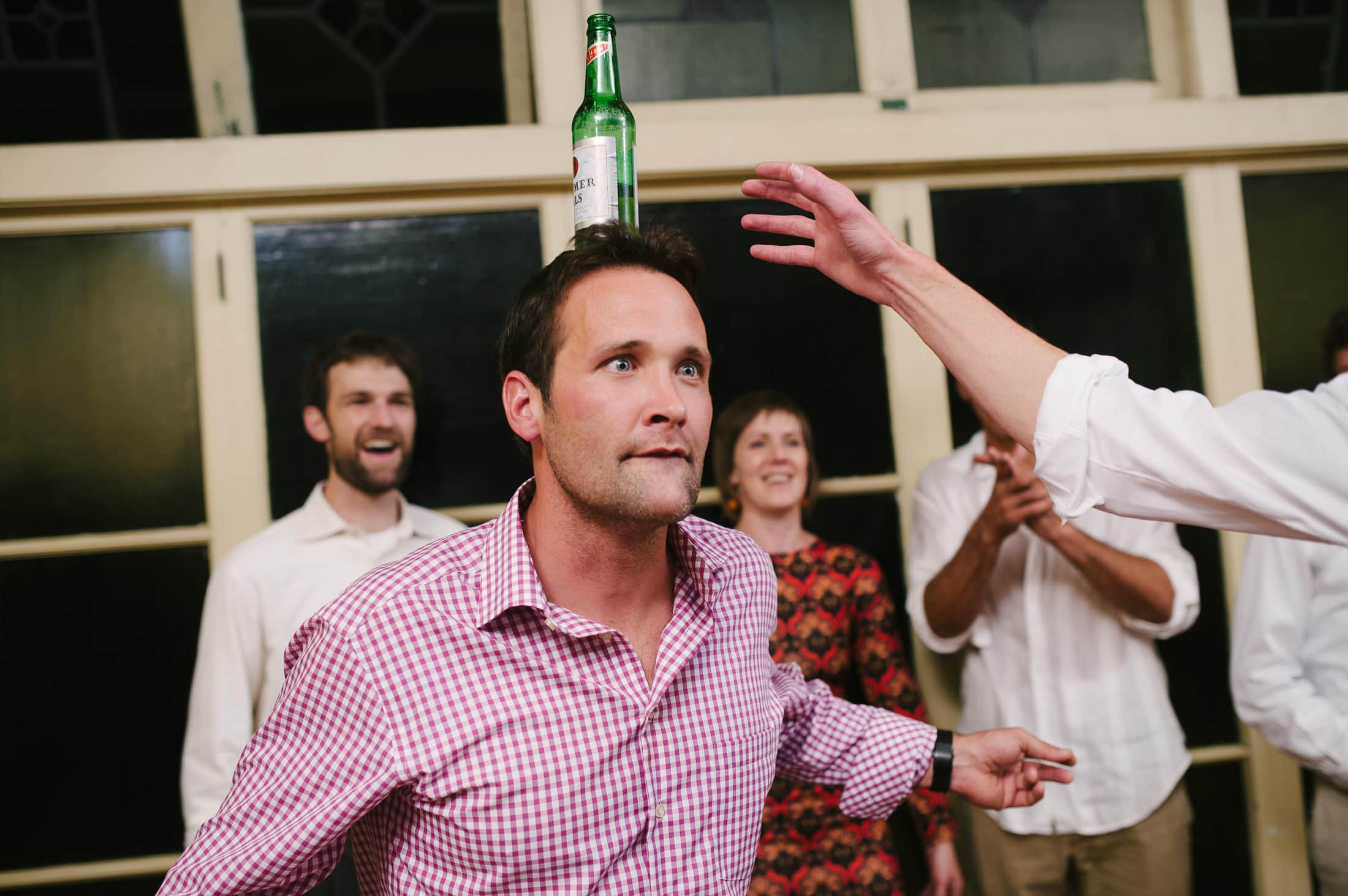 fun dance floor shot of guest balancing beer on head at berkeley wedding